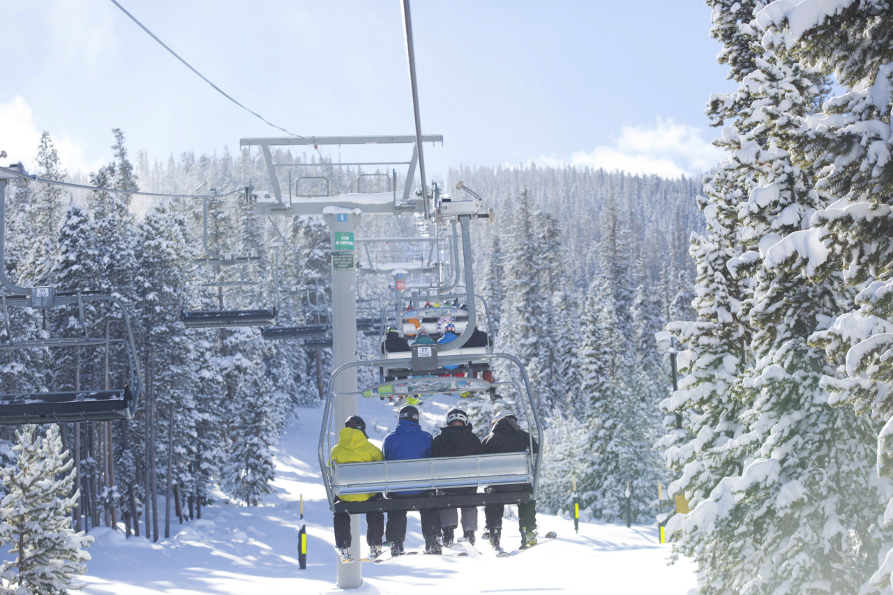 In this Nov. 16, 2014 photo provided by Keystone Resort in Keystone, Colo., skiers take a lift on a snowy mountain. A recent report commissioned by the National Ski Areas Association shows that the percentage of people with household incomes over $100,000 who participate in snow sports has risen over the past eight seasons from 45 percent of ski area visitors to 56 percent of visitors. But there are ways to make a ski trip affordable, including skiing at smaller resorts, buying multi-day, half-day and advance tickets, and taking advantage of discounts for kids, seniors and groups. (AP Photo/Keystone Resort, Cody Mendoza)